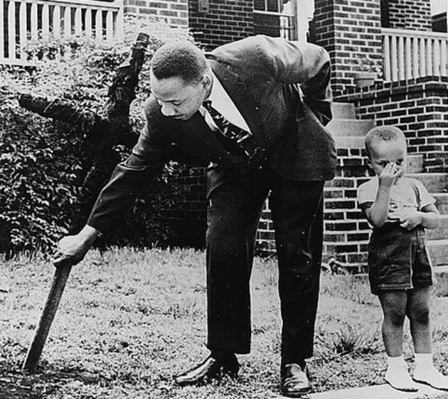 Martin Luther King retirando una cruz quemada en su jardín  junto a su hijo en 1960