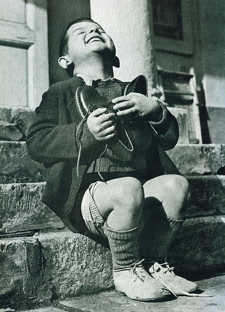 Un niño polaco feliz tras haber recibido un par de zapatos nuevos durante la Segunda Guerra Mundial.