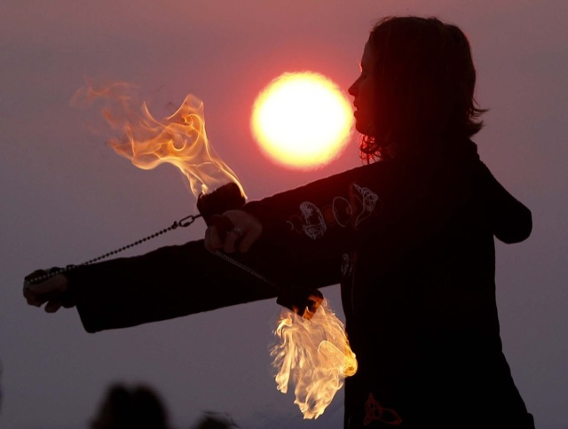 Krissy Humphreys performs with fire at sunrise at the Temple of Whollyness during the BurningMan 2013 arts and music festival in the Black Rock Desert of Nevada