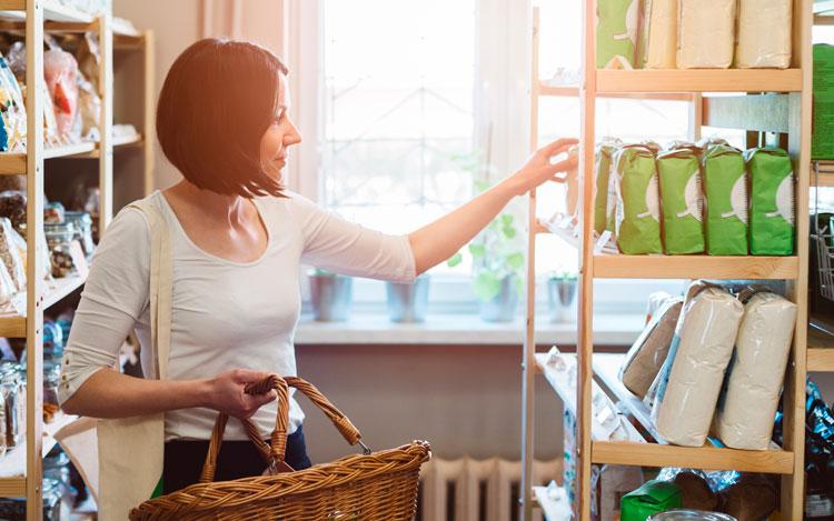Mujer comprando en supermercado productos sostenibles