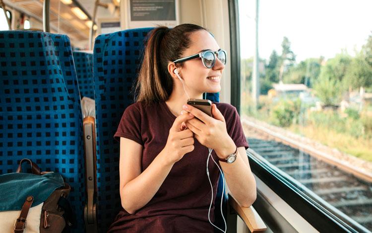 Chica escuchando podcast en el tren